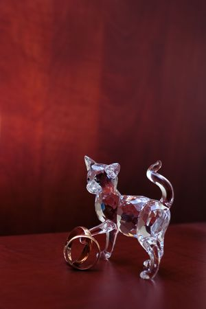 Cut-glass crystal cat with two wedding rings against blurred dark red wood background, selective focus