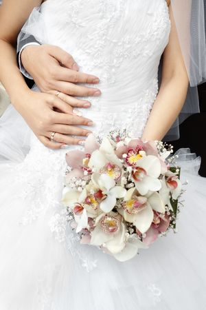 Bride and groom hands on white wedding dress with blurred flowers bouquet