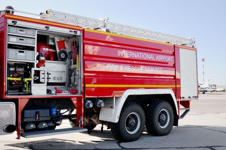 Airport fire truck with opened section with internal mechanisms and devices on tarmac