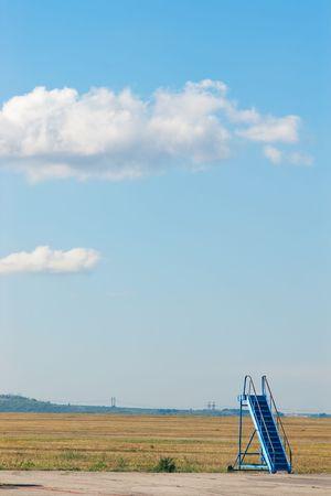 Scalinata di vecchio aereo blu su base aerea contro il cielo blu con attenzione selettiva   Archivio Fotografico