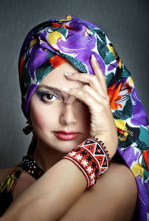 Fashion portrait of girl in ethnic vivid head scarf and bracelet with hand closing one eye, selective focus