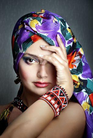Ritratto di moda della ragazza in etnica foulard vivido e bracciale con la mano, chiudendo un occhio, messa a fuoco differenziale Archivio Fotografico