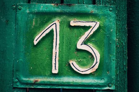thirteen: Cyan grungy tin house plate number 13 with green peeling wooden fence and selective focus