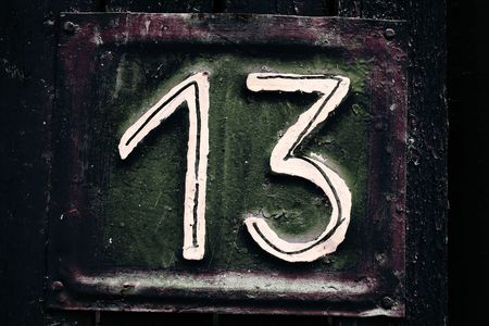 thirteen: dark desaturated grungy tin house plate number 13 with peeling wooden fence and selective focus Stock Photo