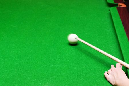Closeup of female hand hitting with billiard cue a white ball in motion with selective focus Stock Photo - 5840752