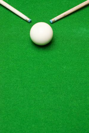 cue sticks: Ends of two pool cue sticks pointing at white ball against green baize texture with selective focus