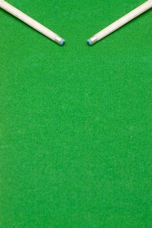 cue sticks: Ends of two pool cue sticks against green baize texture with selective focus and copy space