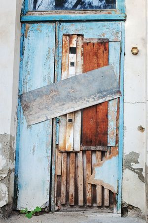 boarded: Old deserted blue door closed and boarded up by tin and wooden plates with green plant growing at the bottom