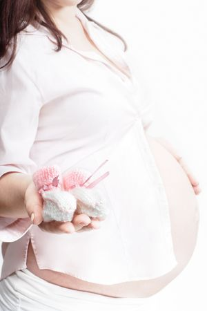 Pregnant woman holding pink and white baby bootee with selective focus Stock Photo - 6229625