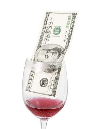 Closeup of wine glass with cracked bottom and one hundred dollar bill inside isolated on white photo