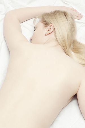 Beautiful blonde lying with naked back and selective focus photo