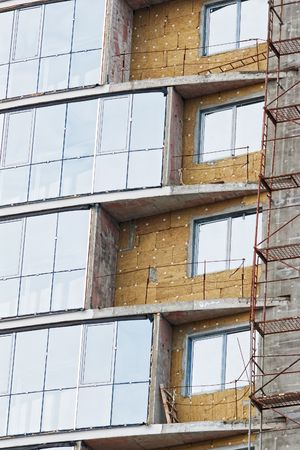 scaffolds: Building under construction with heat insulation and windowed balconies