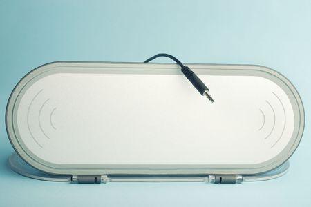 Flat panel audio speaker with mini jack plug on cyan background photo