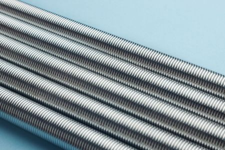 Rows of metal coil springs on blue background with selective focus photo