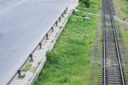 Green grass between highway asphalt road and railroad tracks from top view photo