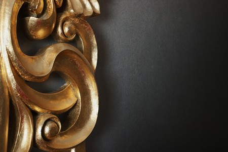 Part of golden stucco decoration in curve shape against dark wall with copy space photo