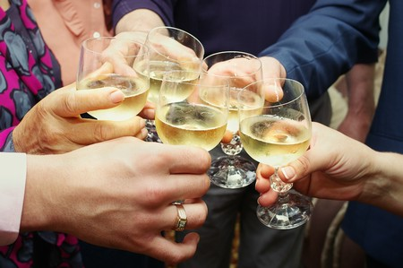 Closeup di molte mani rendendo Brindisi con champagne con fuoco  Archivio Fotografico