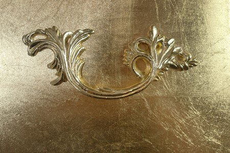 Closeup of carved handle decoration against golden texture photo