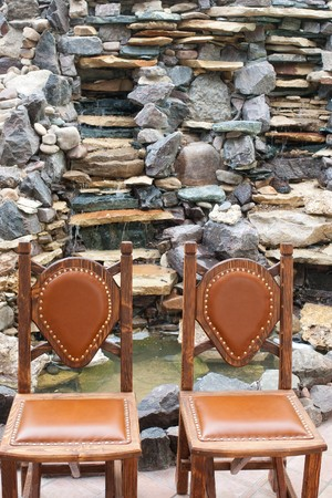 Two wooden chairs with straight back against stone decorated waterfall photo