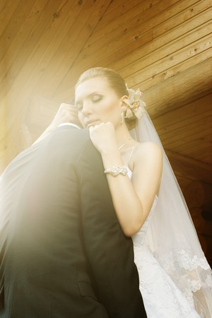 bride embracing groom with closed eyes and sunny flare against blurred wooden house logs photo