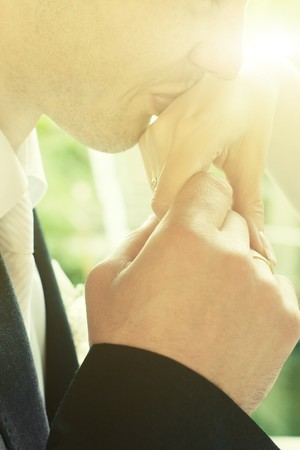 Closeup of groom kissing hand of bride with sunny flare and selective focus on rings photo