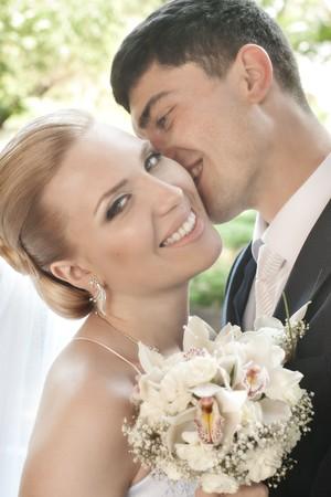 Sposa felice essere baciata nella guancia da sposo con fuoco
