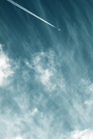 Airplane contrail against sky with diffused white clouds with copy space