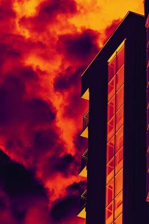 Stylized building façade with balconies against fiery sky with smoke