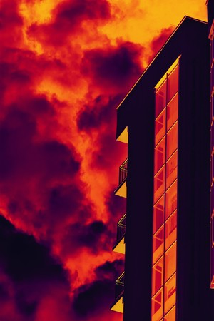 Stylized building fa�ade with balconies against fiery sky with smoke  Stock Photo