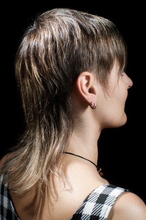 short back: Boyish short haircut of a young woman viewed from side against dark background