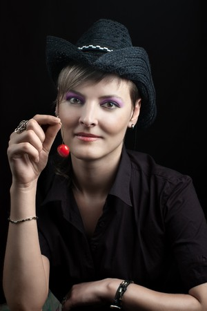 Young woman in black hat holding red cherry against dark background photo