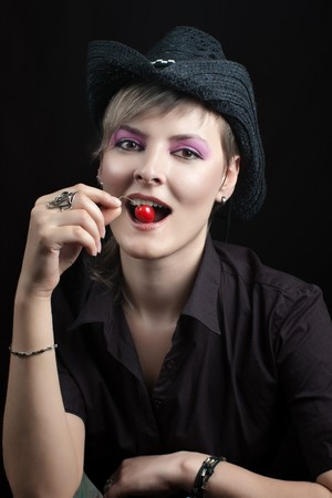 Young woman in black hat with red cherry in mouth against dark background photo