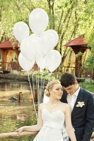 Bride and groom outdoors with white balloons against blurred pond with black swan Stock Photo