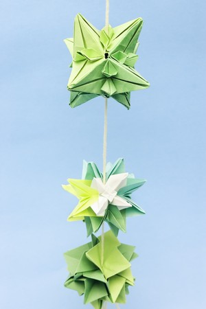 Closeup of abstract shaped green paper origami objects on thread with selective focus on the top one Stock Photo - 7319956