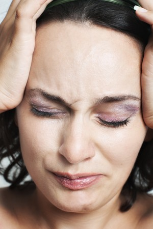 Closeup of young woman suffering from pain and holding her head with selective focus Stock Photo - 7449208