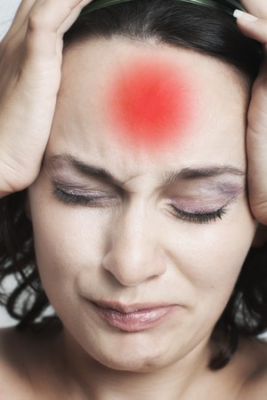 Closeup of young woman with red headache mark on forehead and selective focus Stock Photo - 7449207
