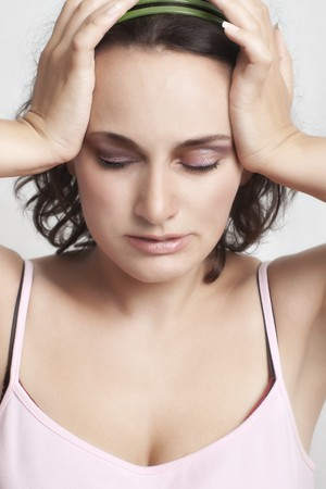 relieved young woman with closed eyes holding her head photo