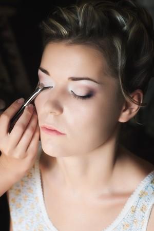 Makeup artist applicando eye shadow sulla bella giovane donna con fuoco