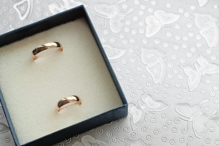 Two wedding rings in box against silver textured butterflies with selective focus Stock Photo - 7753476