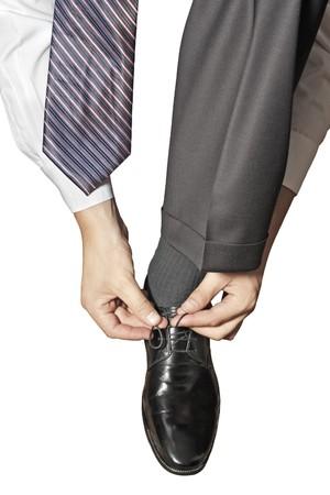 Gamba in pantaloni nella nuova scarpa in pelle nera con shoelace unlaced isolata on white  Archivio Fotografico