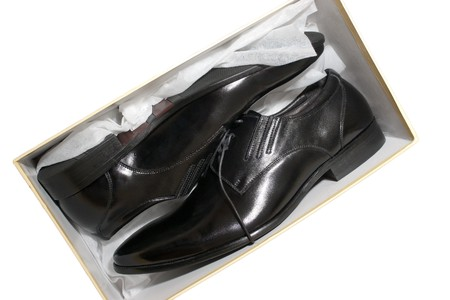 A pair of new black leather shoes inside a box isolated on white photo