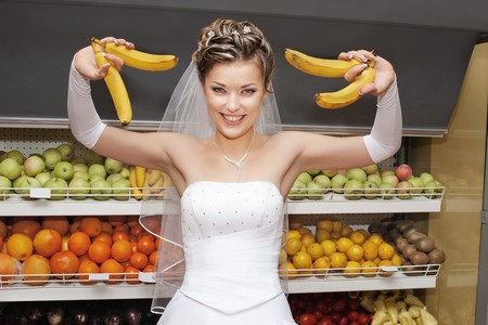 Smiling bride holding bananas in supermarket with shelves of fruits in the background