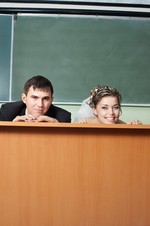 Funny bride and groom faces on classroom table with blackboard behind Stock Photo - 7846386
