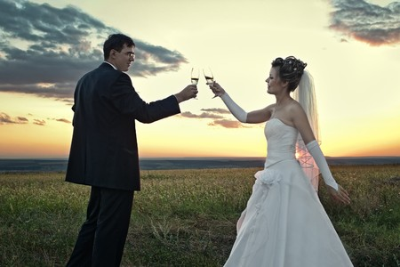 Bride and groom making a toast at sunset in the field outdoors photo