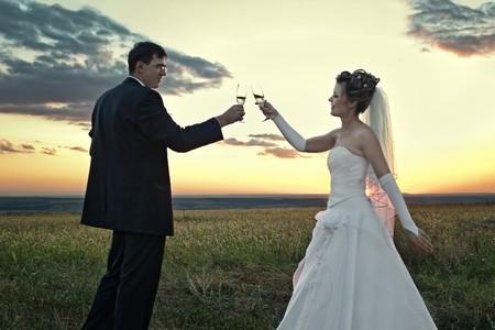 Sposa e lo sposo fare un brindisi al tramonto in mezzo alla natura campo
