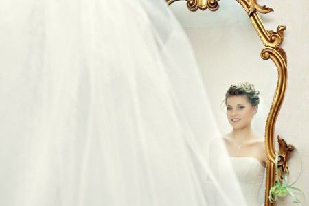 Smiling bride looking at herself in the mirror with golden stucco elements
