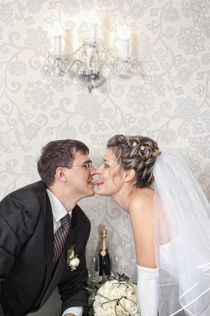 long tongue: Groom kissing bride with a long tongue in stylish indoors  Stock Photo