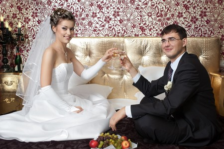 Happy bride and groom making toast on bed in stylish hotel room photo