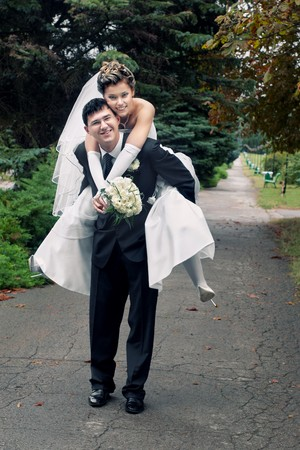 Smiling groom carrying on his back bride outdoors in park with selective focus photo
