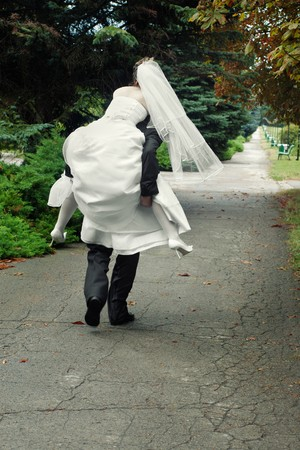 groom running away with bride on his back outdoors in park alley  Stock Photo - 7873973